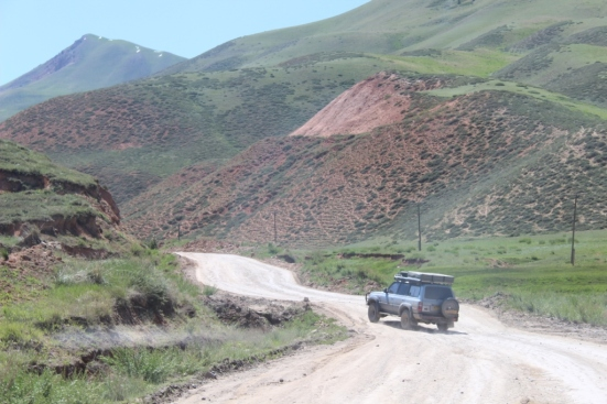 Jon swerves his truck (Boris) to avoid yet another crater in the road